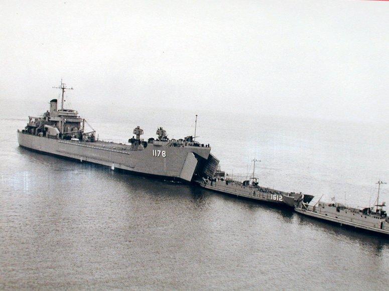 El USS Wood County remolcando dos barcos de la flota